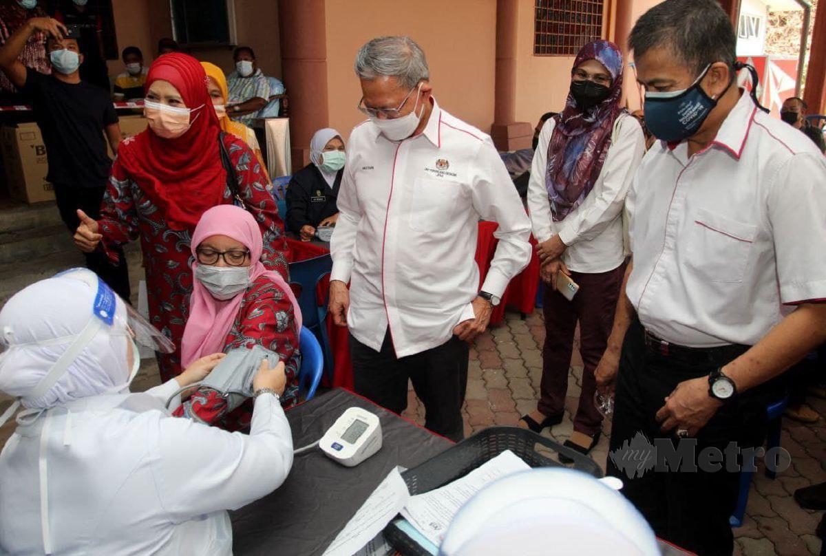 Mustapa (kiri) diiringi Dr Zaini memantau Petugas kesihatan memberi suntikan vaksin Covid-19 kepada penduduk pada Program Outreach Vaksinasi Covid-19 di Perkarangan Dewan Tok Pa di Pusat Khidmat Ahli Parlimen Jeli, Bukit Nangka. FOTO NIK ABDULLAH NIK OMAR