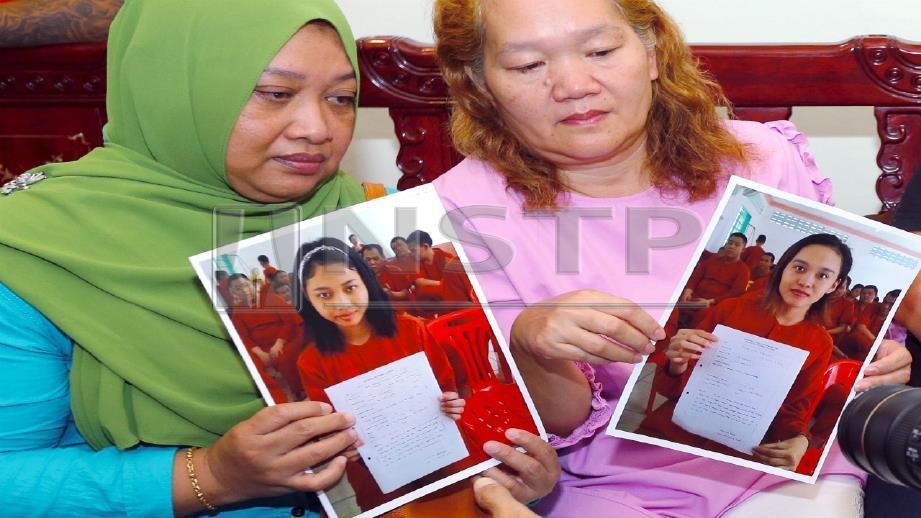 Dua wanita bersama gambar anak perempuan mereka yang dalam tahanan di Kemboja. FOTO Nadim Bokhari.