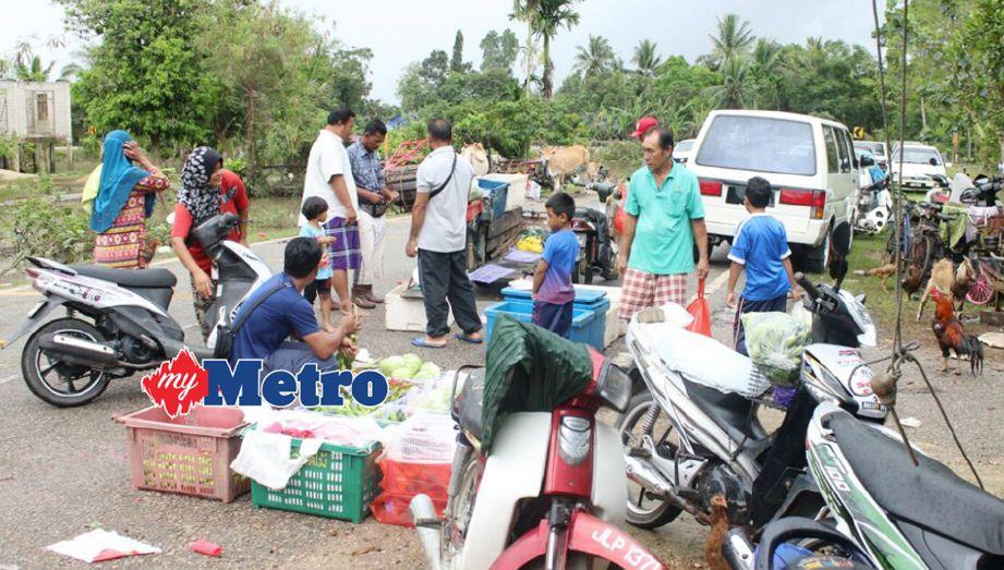 PENDUDUK Kampung Kubang Sawa, Tumpat, membeli keperluaan harian di tepi jalan. FOTO Nik Abdullah Nik Omar