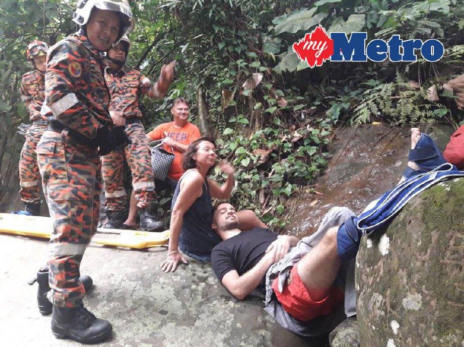 Anggota bomba membantu pelancong Perancis yang patah kaki kanan selepas terjatuh ketika mandi di Air Terjun Kionsom, Inanam, kira-kira 4.30 petang hari ini.