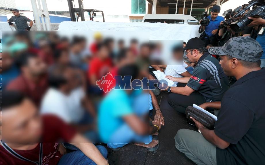 (Gambar fail) Mustafar (duduk dua dari kanan) memeriksa salinan pengenalan diri pekerja asing semasa operasi penguatkuasaan selepas tamat Program 3+1 iaitu program serah diri dan pulang secara sukarela di sebuah kilang di Sepang awl bulan ini. FOTO Ahmad Irham Mohd Noor