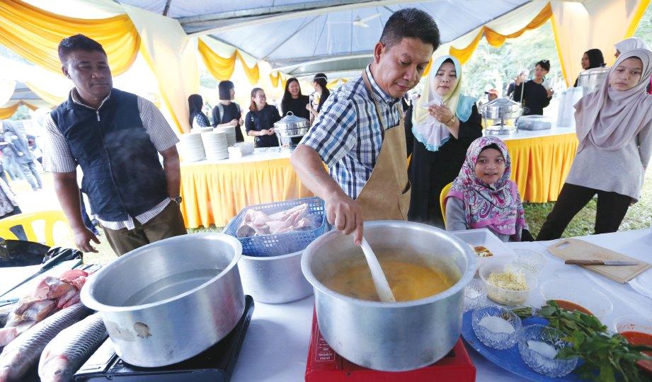 PERTUNJUKAN memasak gulai tempoyak ikan air tawar Sungai Pahang.