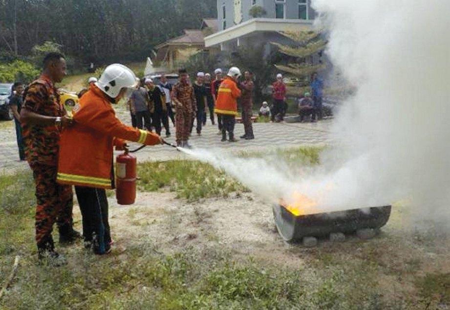 PIHAK bomba mengajar peserta memadam kebakaran.