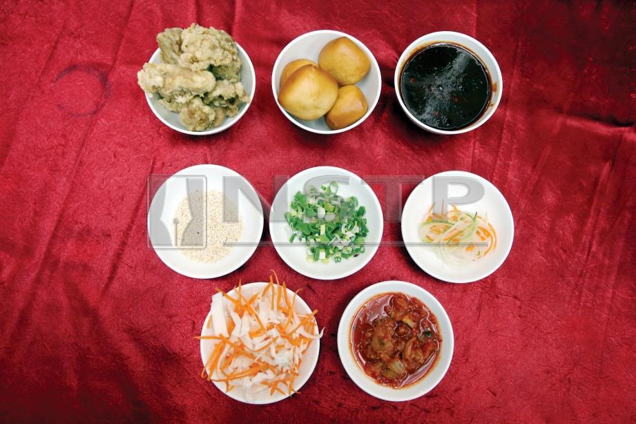 1. BAHAN untuk dakgangjeong sos pedas Korea, kimchi, roti span, daun bawang, bijan, ayam yang sudah digoreng dan sayuran sebagai hiasan.