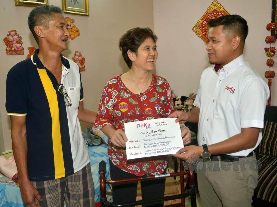 SAU Wan, (tengah) menerima manfaat PeKa B40 daripada wakil ProtectHealth Corporation. FOTO Faiz Anuar