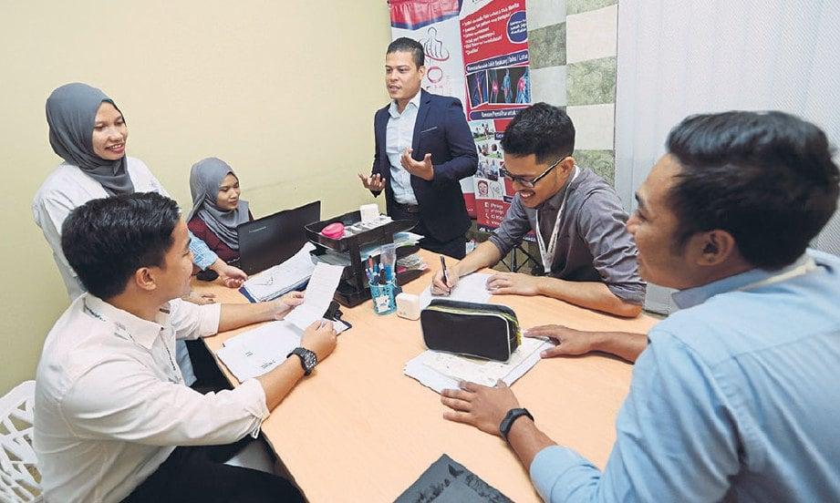 MOHD Arif (berdiri) berbincang dengan ahli fisioterapi.