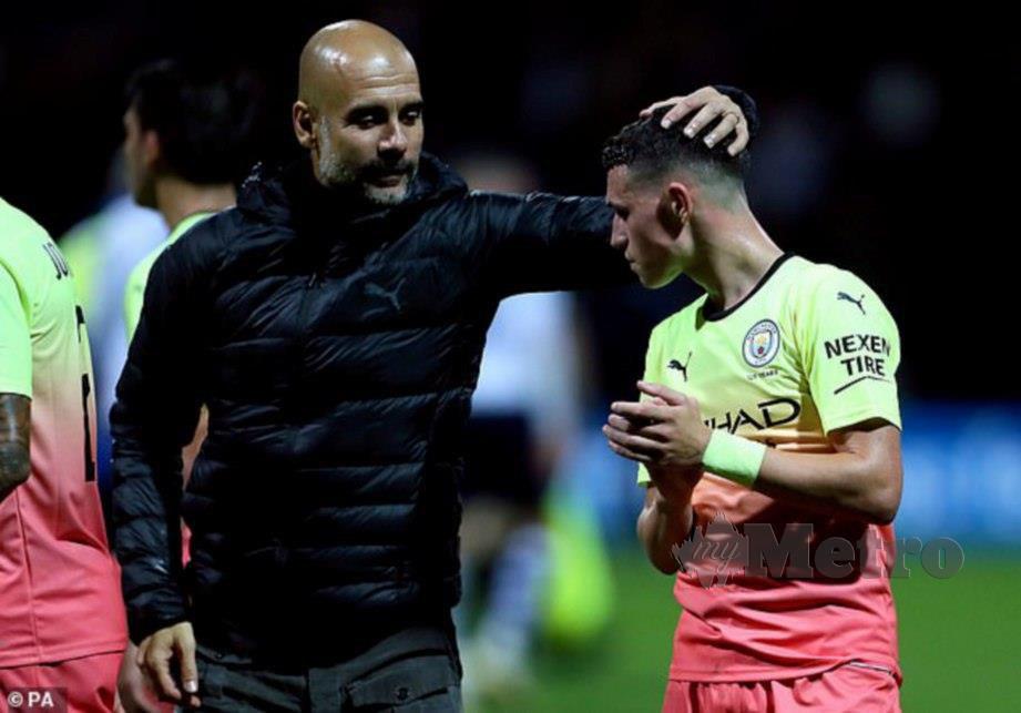 Guardiola (kiri) memberi kata semangat kepada Foden. FOTO Agensi
