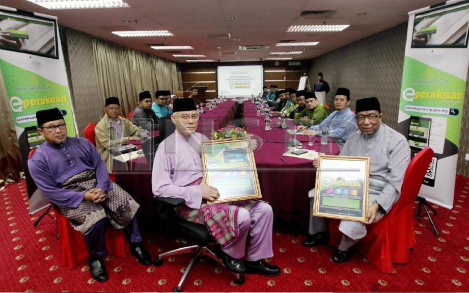 Wan Abdul Wahid (tengah) dan Abdul Rahman (kanan) menunjukkan aplikasi e-perakuan pada sidang media sempena Taklimat Perakuan Kebenaran Mengajar Agama Islam Negeri Pahang. FOTO Muhd Asyraf Sawal