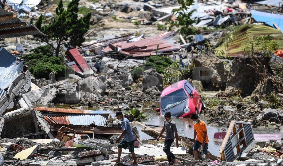 PENDUDUK kampung Balaroa berjalan di atas celah runtuhan kampung mereka yang terjejas teruk. FOTO AFP