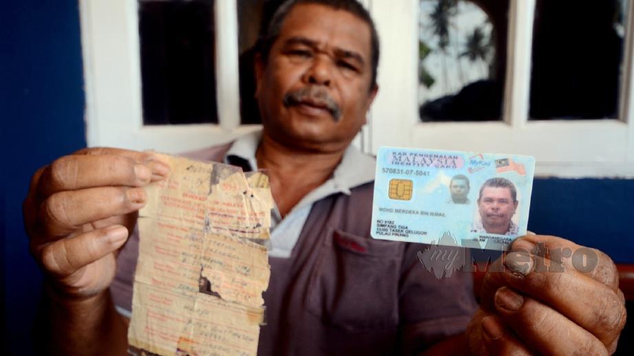 MOHD MERDEKA Ismail, 61, menunjukkan kad pengenalan serta sijil kelahiran semasa ditemui di Kampung Dua Puluh, Penaga. FOTO Shahnaz Fazlie Shahrizal
