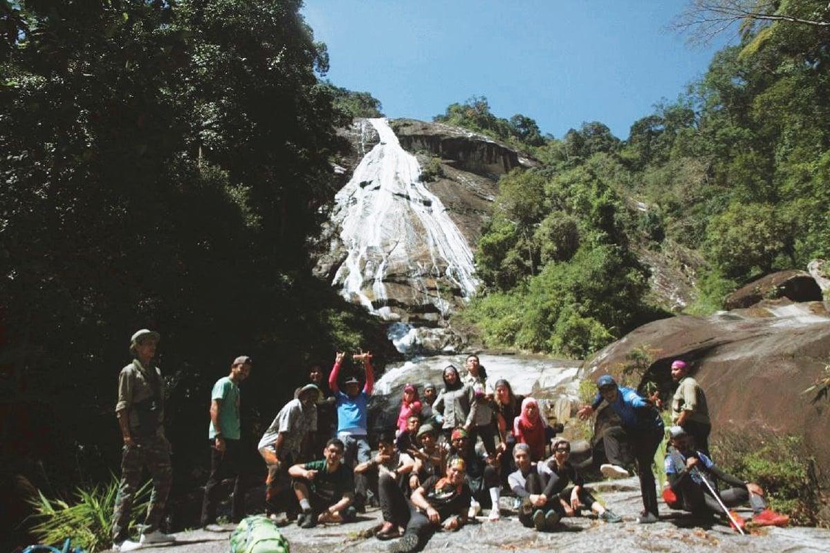 PENDAKI bergambar kenangan dengan berlatarbelakangkan air terjun Gunung Stong.