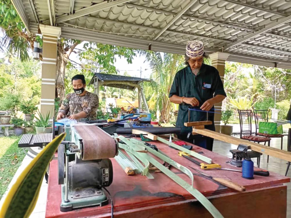SUFYAN (kanan) menunjukkan cara memintal benang untuk penghasilan busar.