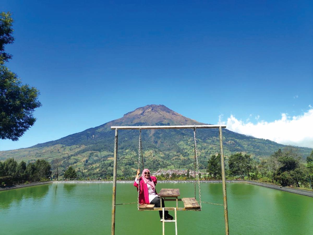 PENULIS merakam kenangan di atas buaian dengan berlatarbelakangkan danau dan gunung.
