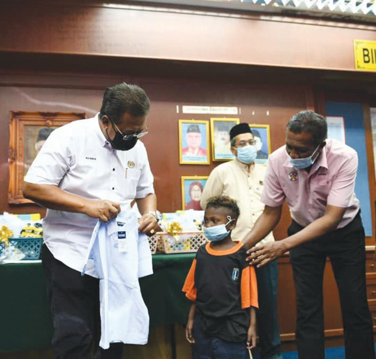 ABDUL Rahman memakaikan seragam sekolah kepada wakil murid.