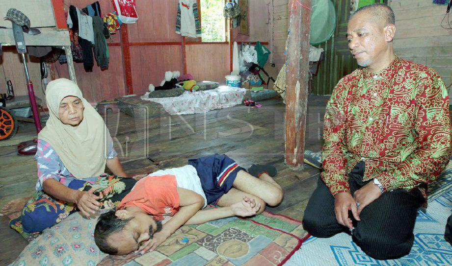 WARGA emas, Che Eshah Mat Zain, 64, tetap menjaga dan menguruskan anaknya Muhamed Daud 46, yang hilang upaya akibat lumpuh sejak pertengahan tahun lalu selepas kemalangan pada 2016 ketika ditemui di rumahnya di Kampung Siti Manis dekat Pantai Cahaya Bulan (PCB). FOTO Syamsi Suhaimi