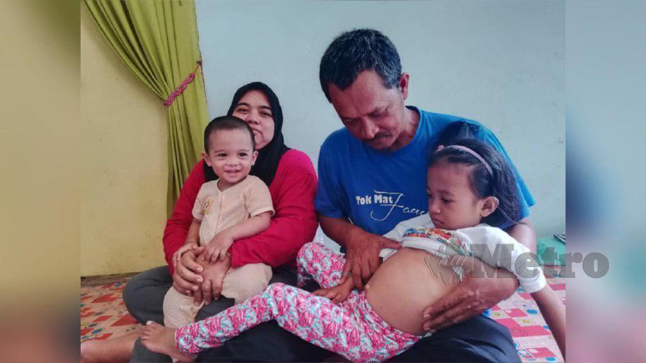 AZAHAR menunjukkan perut anaknya, Nur Fathiah Najwa yang besar kerana mengalami pembesaran hati dan limpa disebabkan jangkitan kuman. FOTO Noor Hidayah Tanzizi