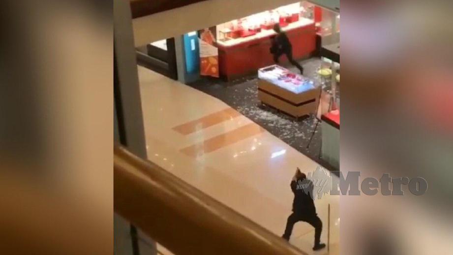 PENGAWAL keselamatan mengacu pistol ke arah perompak. FOTO video tular
