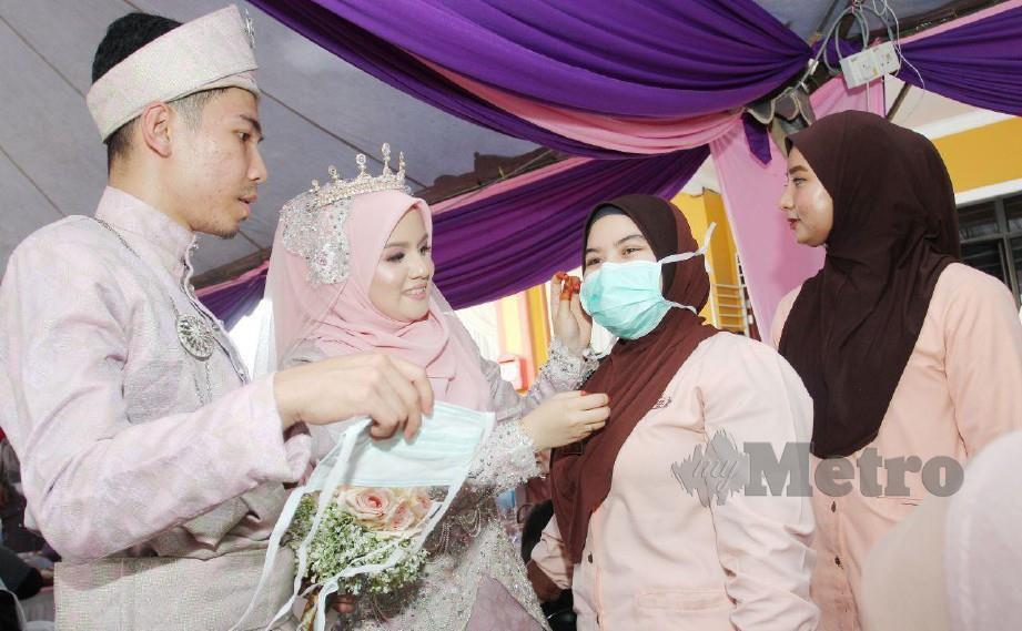 SEPASANG pengantin baru, Farkhan dan isteri, Nur Tasnim memakai topeng muka kepada tetamu yang hadir pada majlis perkahwinan mereka di Kampung Tebing Tinggi, Kubang Kerian. FOTO NIK ABDULLAH NIK OMAR
