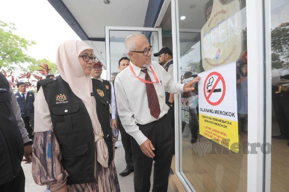 Dr Bahari Muda menampal notis amaran larangan merokok di premis makanan pada program Walkabout Bebas Asap Rokok di Tempat Makan di Jalan Tun Ismail. FOTO MOHD RAFI MAMAT