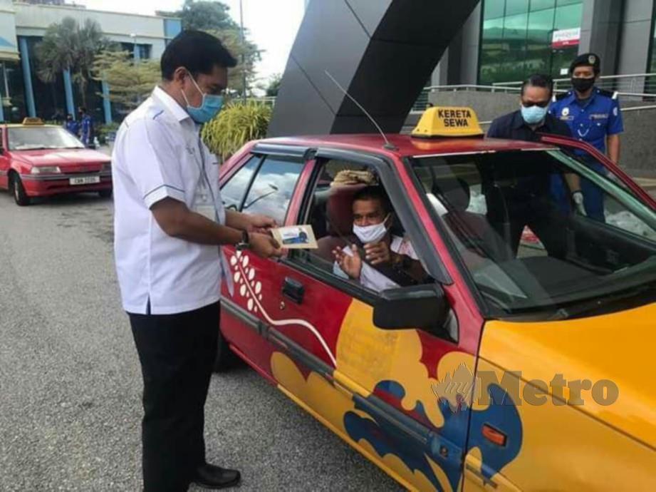 HAMDAN Hussin (kiri) menyampaikan bantuan khas kepada pemandu teksi secara pandu lalu di perkarangan ibu pejabat MPK, Kuantan. FOTO IHSAN MPK