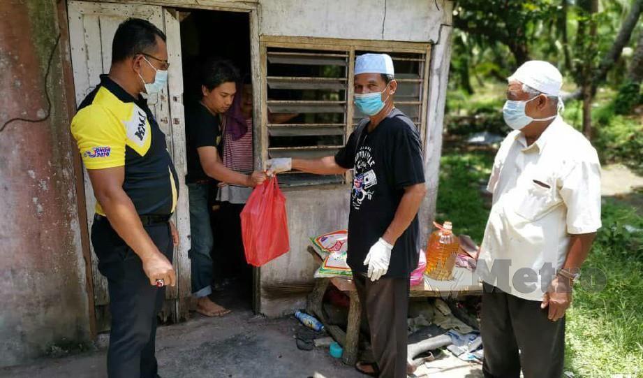 AIDIL Aziz Hanafi (kiri) mengagihkan bantuan khas bekalan makanan kepada keluarga terjejas di kawasan pentadbirannya. FOTO IHSAN PEJABAT PENGHULU