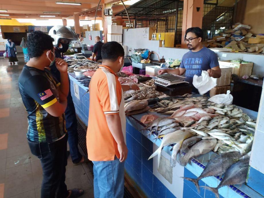Saifuddin sedang melayan pelanggan di gerai ikannya di Pasar Bukit Besar, Kuala Terengganu. FOTO Ahmad Rabiul Zulkifli