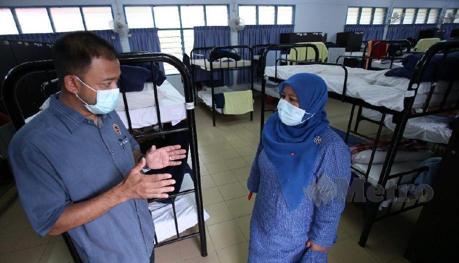 PENGERUSI Jawatankuasa Pembangunan Wanita, Keluarga dan Masyarakat Johor, Zaiton Ismail (kanan) bersama Pegawai Daerah Kluang, Mohd Radzi Mohd Amin meninjau bilik dorm yang menempatkan seramai 237 gelandangan, di Kem Wawasan Bina Negara, Gunung Pulai, di Kulai, akan dikuarantin di lokasi berkenaan sepanjang musim wabak COVID-19 ini. FOTO Mohd Azren Jamaludin