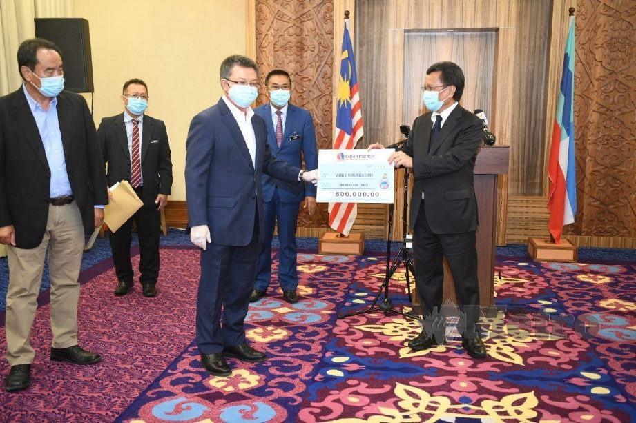 Mohd Shafie (kanan) menerima replika cek daripada salah satu Syarikat Berkaitan Kerajaan (GLC) sempena Majlis Penyerahan Sumbangan GLC kepada Tabung Bencana Negeri Sabah di Kota Kinabalu. FOTO YUN MIKAIL