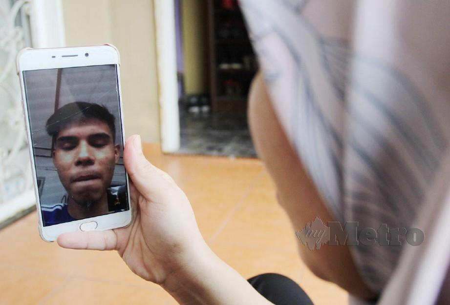 Vivi Sumanti sedang menghubungi anaknya Ahmad Shahfaris  yang kini menuntut di Politeknik Ungku Omar, Ipoh. FOTO NIK ABDULLAH NIK OMAR.