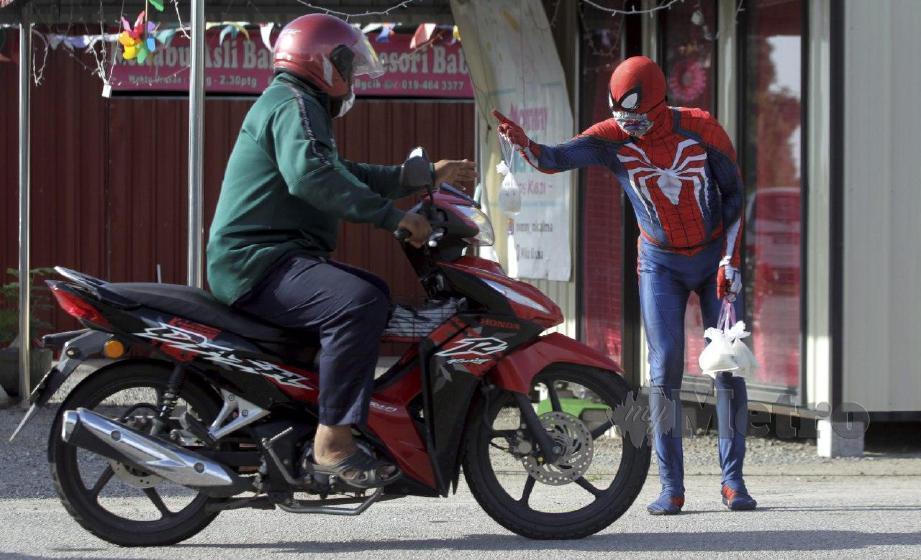 Antara sekumpulan 'super hero' menyerahkan bubur lambuk kepada orang ramai yang melalui Jalan Sungai Dua di sini. Sebanyak 450 bungkus bubur hasil sumbangan rakan-rakan kostum diberi nama 'Geng Superhero Penang', antara rakan kostum terlibat ialah Ultraman Zero, Spiderman, Kamen Rider, Power Rangers, dan Badut yang turut mengenakan penutup hidung dan mulut. FOTO DANIAL SAAD