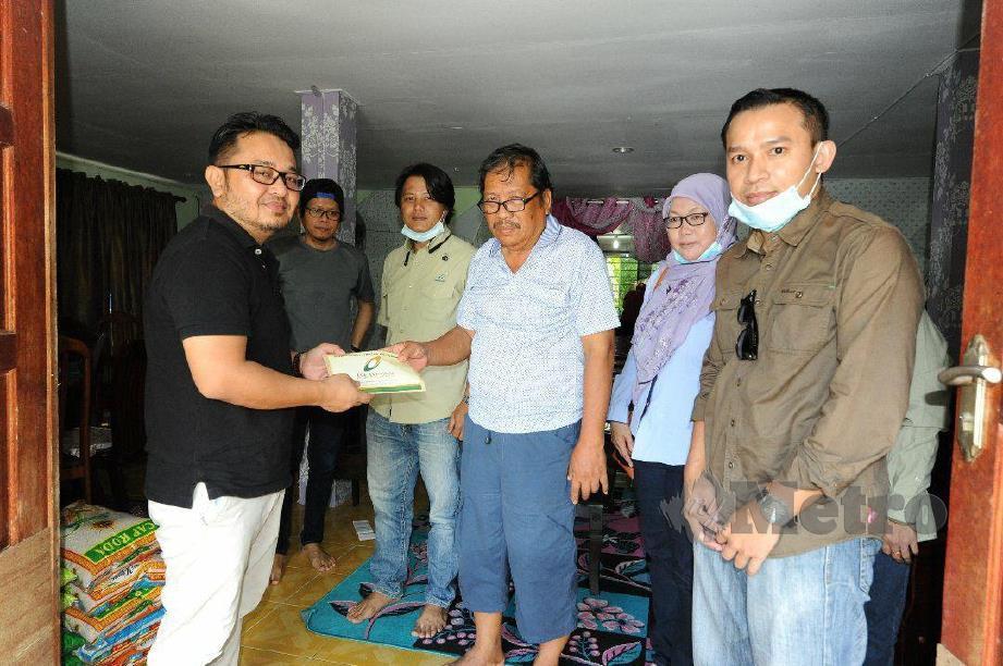 Jasnih (kiri) menyampaikan sumbangan kepada Othman Ali di Kampung Sungai Damit, Membakut. - FOTO / BERNAS