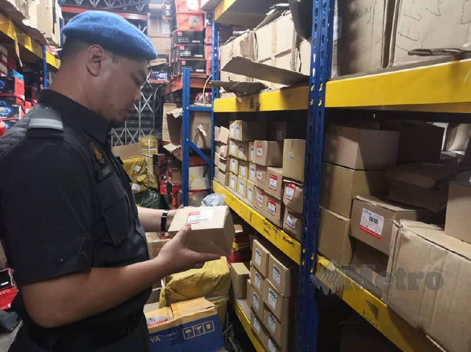 Pegawai penguat kuasa KPDNHEP membuat pemeriksaan ke atas sebuah syarikat menjual alat ganti motosikal tiruan di Kepong.  FOTO Ihsan KPDNHEP