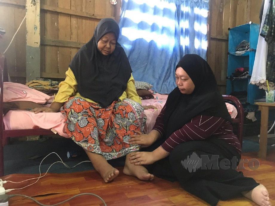 Nur Fadilah Hashim (kanan) menguruskan keperluan ibunya, Faridah Taib (kiri) yang menghidap penyakit buah pinggang tahap lima ketika ditemui di rumah mereka di Kampung Bechah, Tanjung Mas. FOTO/ HAZIRA AHMAD ZAIDI
