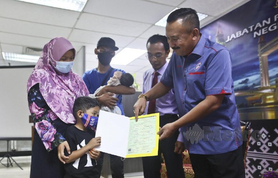 RUSLIN (kanan) menyerahkan dokumen pengenalan diri kepada Nor Erdaliana Mohd Saufi, 32, bersama anaknya, Muhammad Khairul Izham Abdullah pada majlis berlangsung di JPN Kuala Terengganu. FOTO Ghazali Kori.