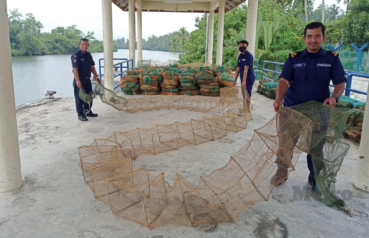 Anggota Perlindungan Sumber Perikanan memeriksa bubu Naga yang berjaya dirampas. FOTO NIK ABDULLAH NIK OMAR