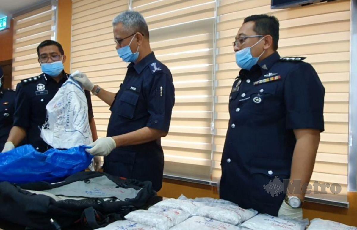 Hasanuddin Hassan (tengah) memeriksa guni yang digunakan penjenayah untuk menyembunyikan dadah heroin. FOTO HAMZAH OSMAN