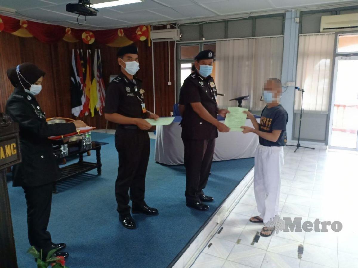 Ahmad Saidi Hamzah menyerahkan sijil PBSL kepada penghuni yang terpilih di Penjara Marang. FOTO AHMAD RABIUL ZULKIFLI