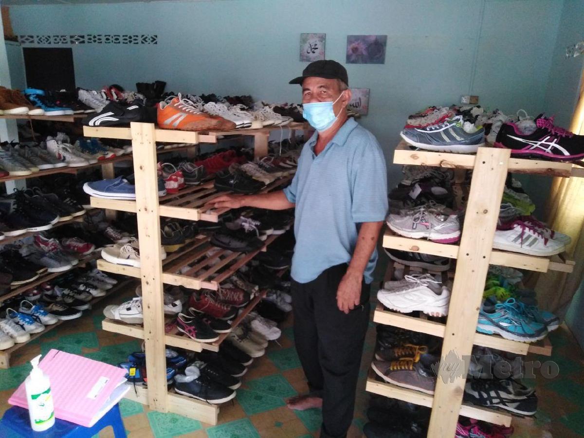 Zain Ahmad menunjukkan kasut yang dilarikan pencuri dari rak di premis miliknya di Kampung Bukit Kuching Tengah, Jeram, hari ini. FOTO AMIRUL AIMAN HAMSUDDIN