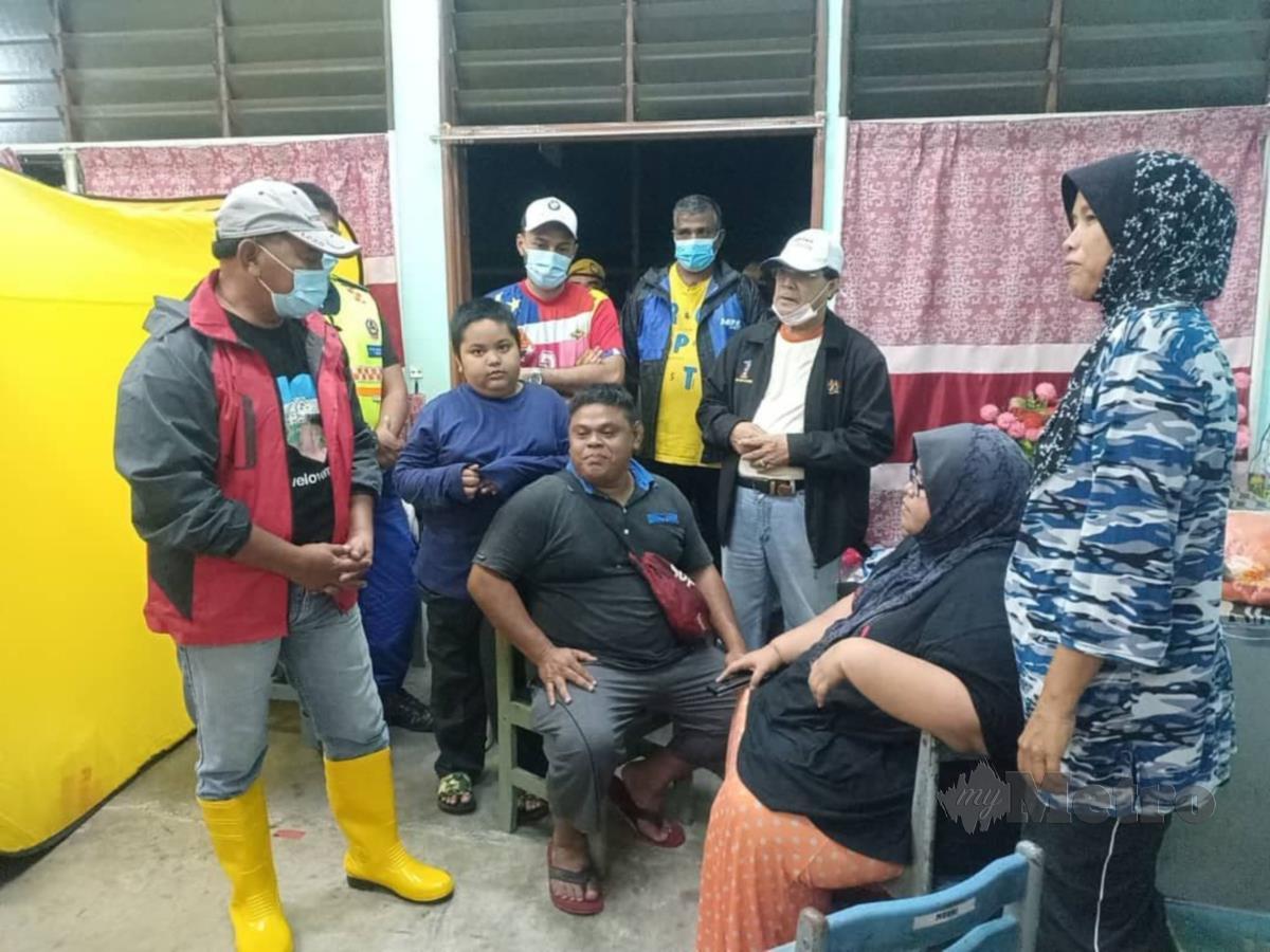 ADUN Ayer Molek, Datuk Rahmad Mariman (kiri) bertanya sesuatu kepada mangsa banjir yang ditempatkan di PPS SK Ayer Molek, malam ini. FOTO AMIR MAMAT