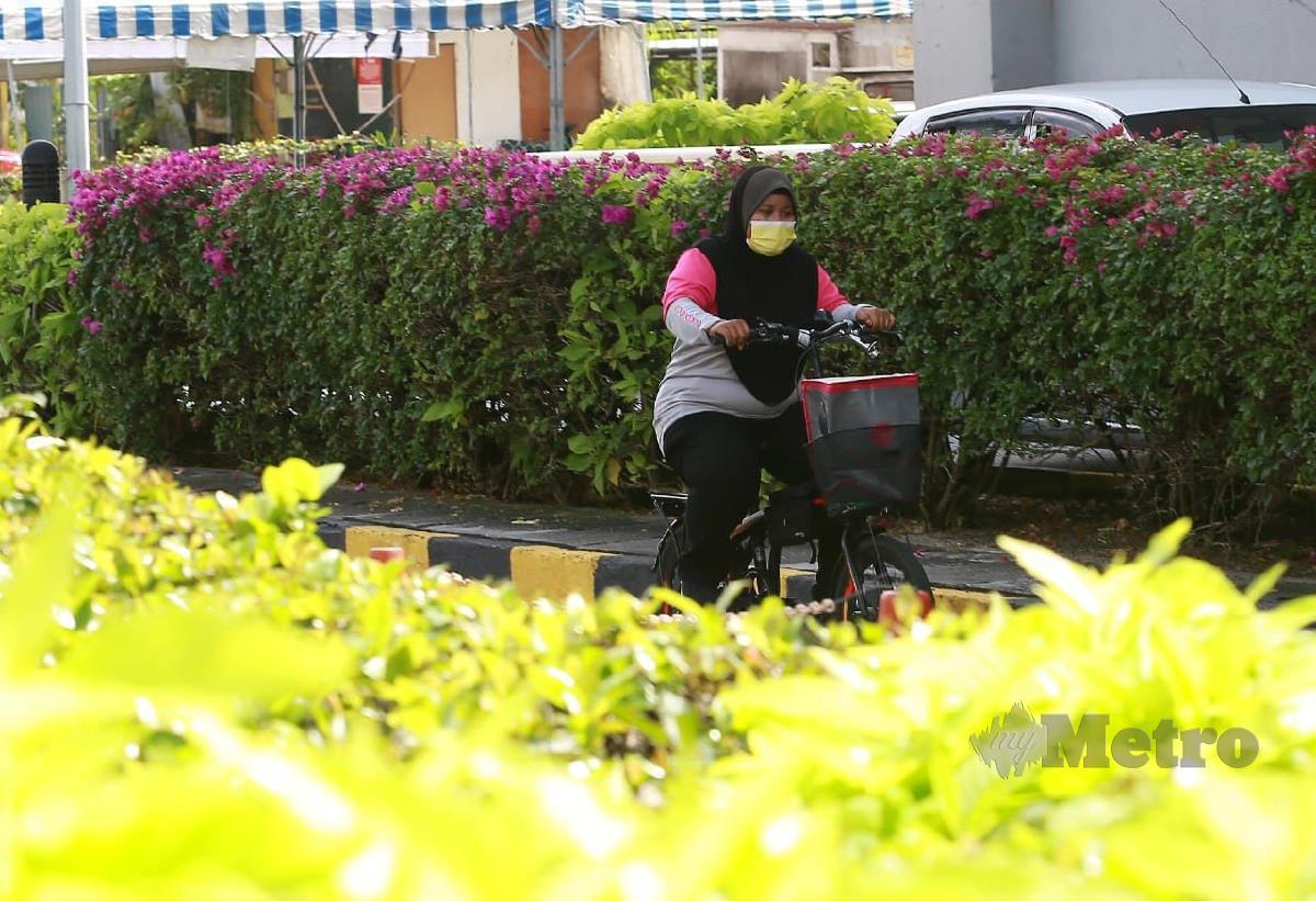 Siti Khadijah menggunakan basikal untuk menghantar makanan di sekitar Ipoh. FOTO SHARUL HAFIZ ZAM
