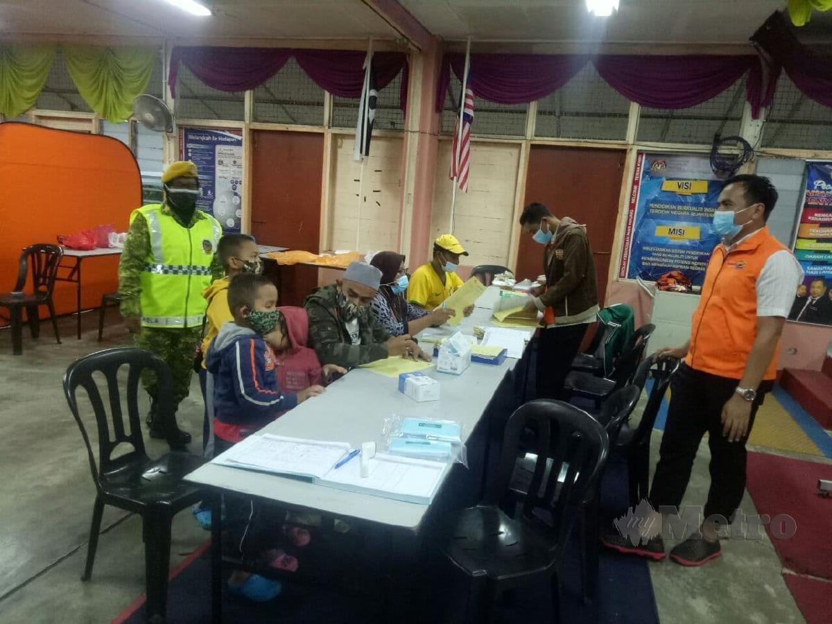 Mangsa banjir terbaru mendaftarkan diri di PPS SK Pasir Panjang, petang ini. FOTO BAHAROM BAKAR.