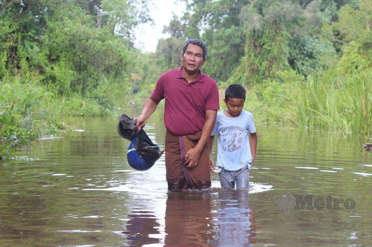 MOHD Zawawi bersama anaknya Mohd Faris keluar membeli keperluan harian selepas rumah mereka ditenggelami banjir. FOTO Nor Amalina Alias