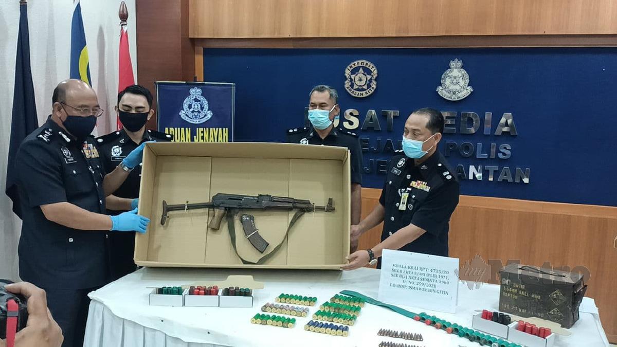 Shafien Mamat (kiri) menunjukkan senjata jenis AK47 yang dirampas daripada seorang petani di Kampung Bahagia, Kuala Krai, malam Ahad lalu. FOTO SITI ROHANA IDRIS