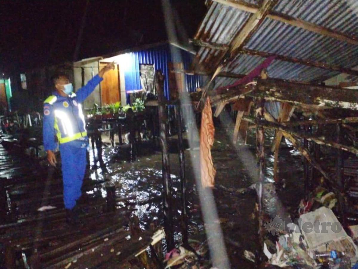 Salah seorang anggota APM menunjukkan rumah yang roboh akibat fenomena air pasang di Kudat semalam. FOTO ihsan APM Kudat