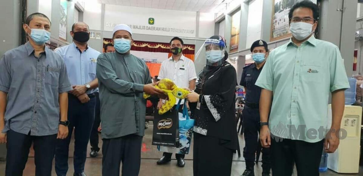 Ariffin (tiga kiri) menyampaikan sumbangan kepada petugas barisan hadapan di PPV Kuala Berang. FOTO/BAHAROM BAKAR
