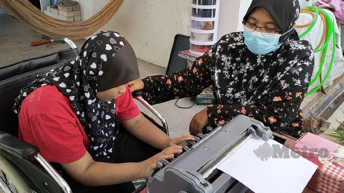 HASSILAWATI (kanan) melihat anaknya, Nur Ain Balqis yang kini buta belajar menggunakan mesin braille di rumah mereka. FOTO Zuliaty Zulkiffli