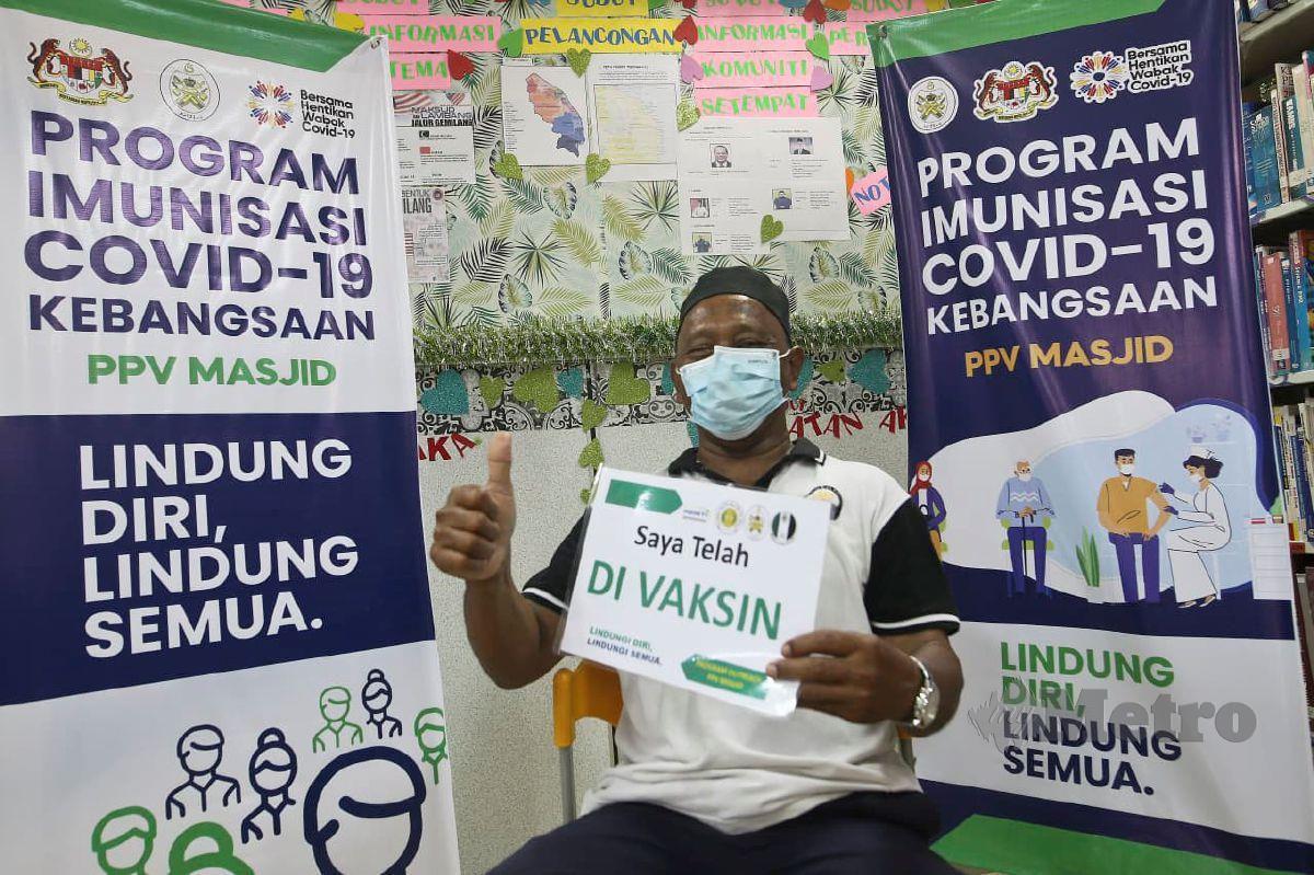ABD Razak memegang plakad 'Saya telah divaksin'  selepas menerima suntikan vaksin Covid-19 di PPV Masjid At-Taqwa. FOTO Ghazali Kori