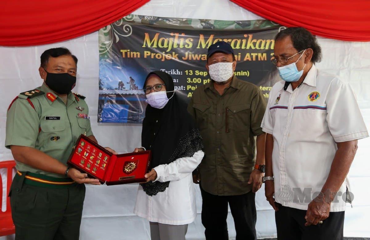 Saifulisham Baharun (kiri)) menyampaikan cenderahati kepada Faridah di Kampung Pelangai. FOTO AZRUL EDHAM MOHD AMINUDDIN