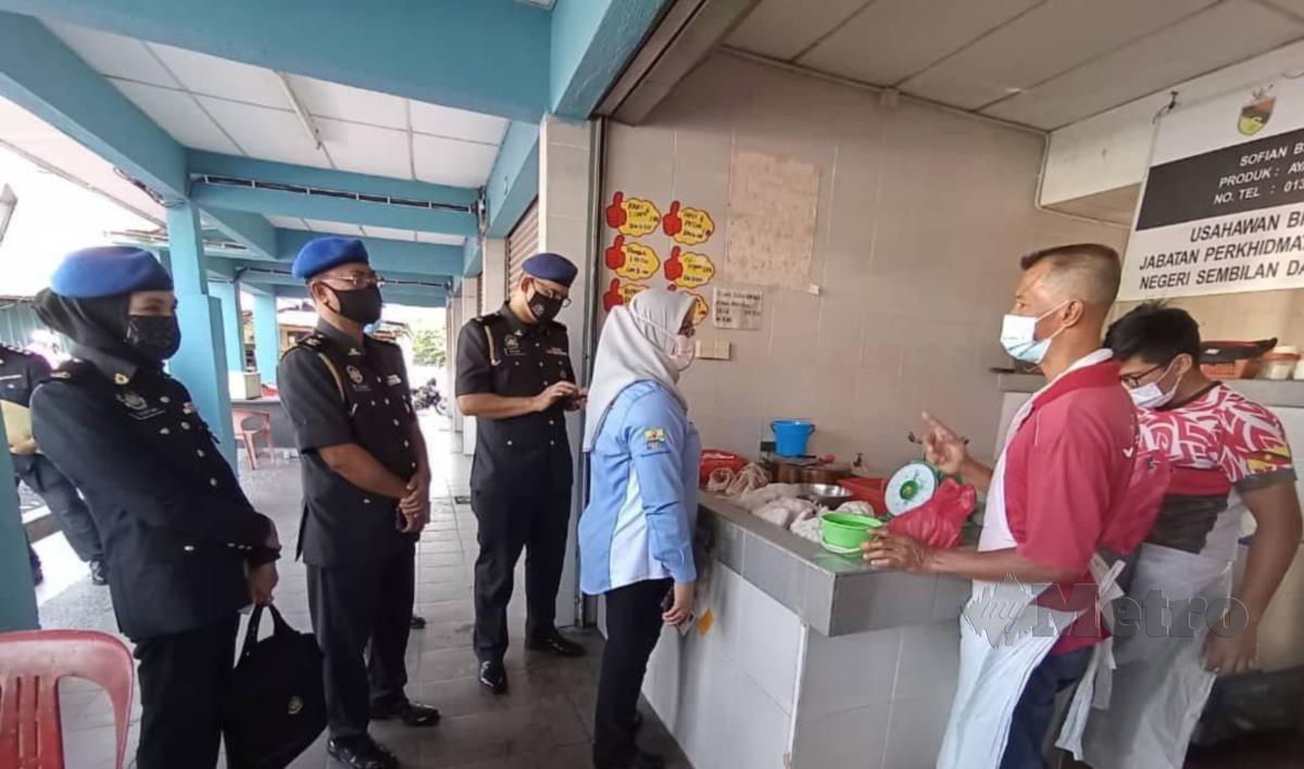 Ain Arjuna Aziz Zaman membuat pemeriksaan harga ayam di Pasar Awam Kuala Pilah, pagi tadi.