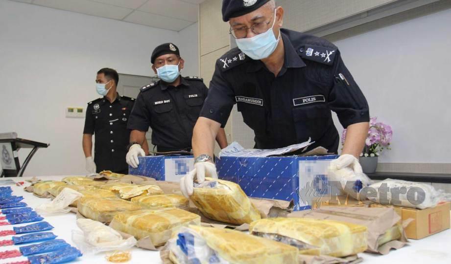 HASANUDDIN (kanan) menunjukkan rampasan 140,000 biji dipercayai pil yaba bernilai RM1.4 juta ketika sidang media di Ibu Pejabat Polis Daerah (IPD) Pasir Mas. FOTO Nik Abdullah Nik Omar